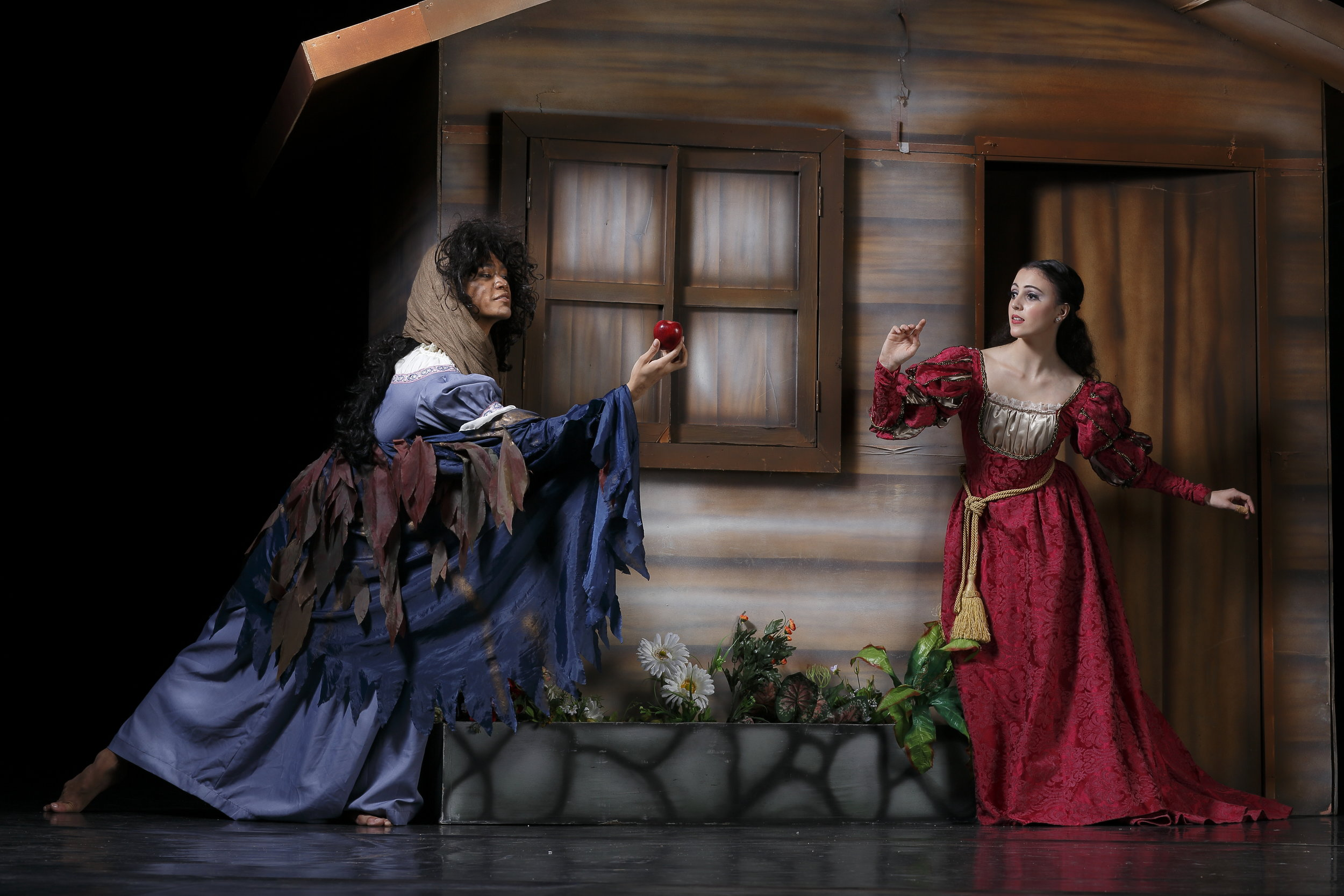 The Witch (Godwin Merano) entices Snow White (Katherine Barkman) to take a bite out of the poisoned apple.