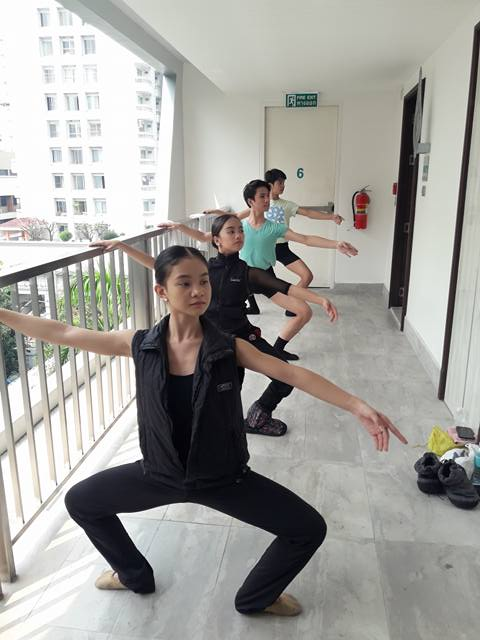 The four dancers take class in the corridor outside their hotel rooms.