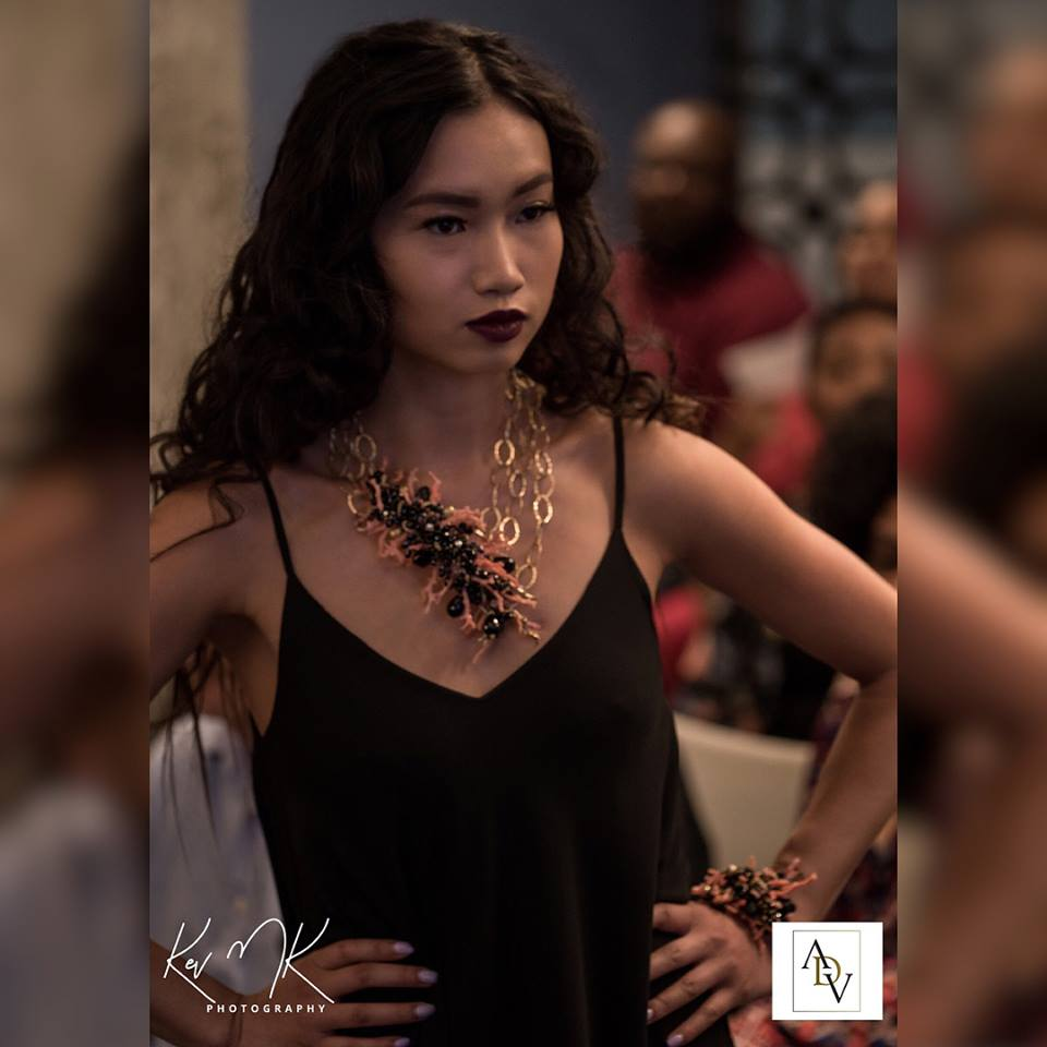 Model wearing branch coral, black spinel, onyx and gold statement necklace