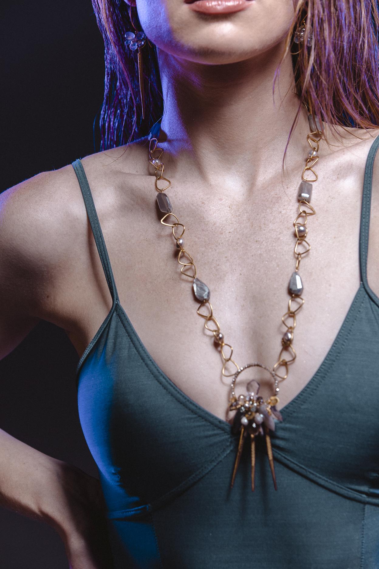 Model wearing long gemstone pendant necklace