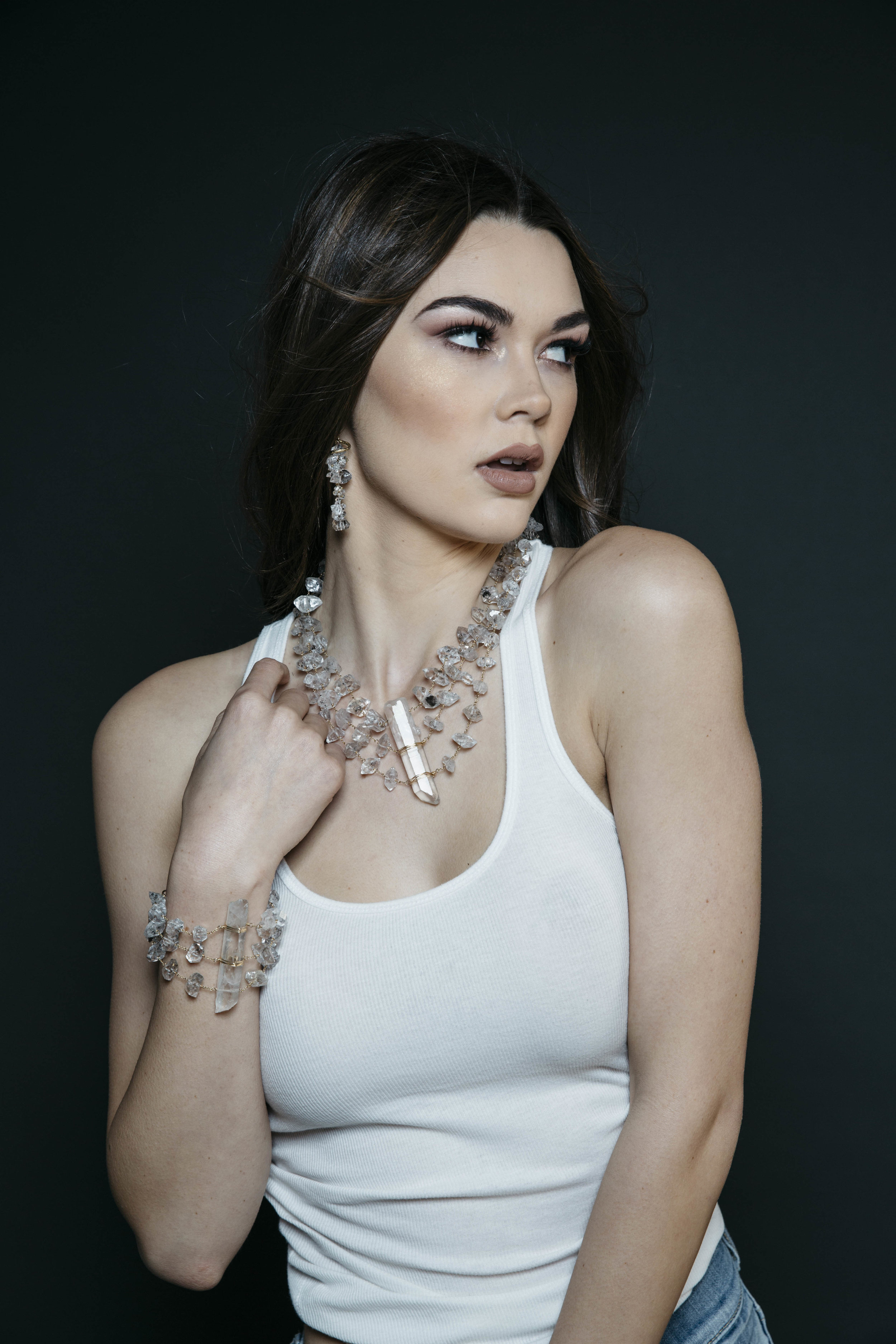 Model wearing a triple strand herkimer diamond statement necklace with a large crystal point pendant
