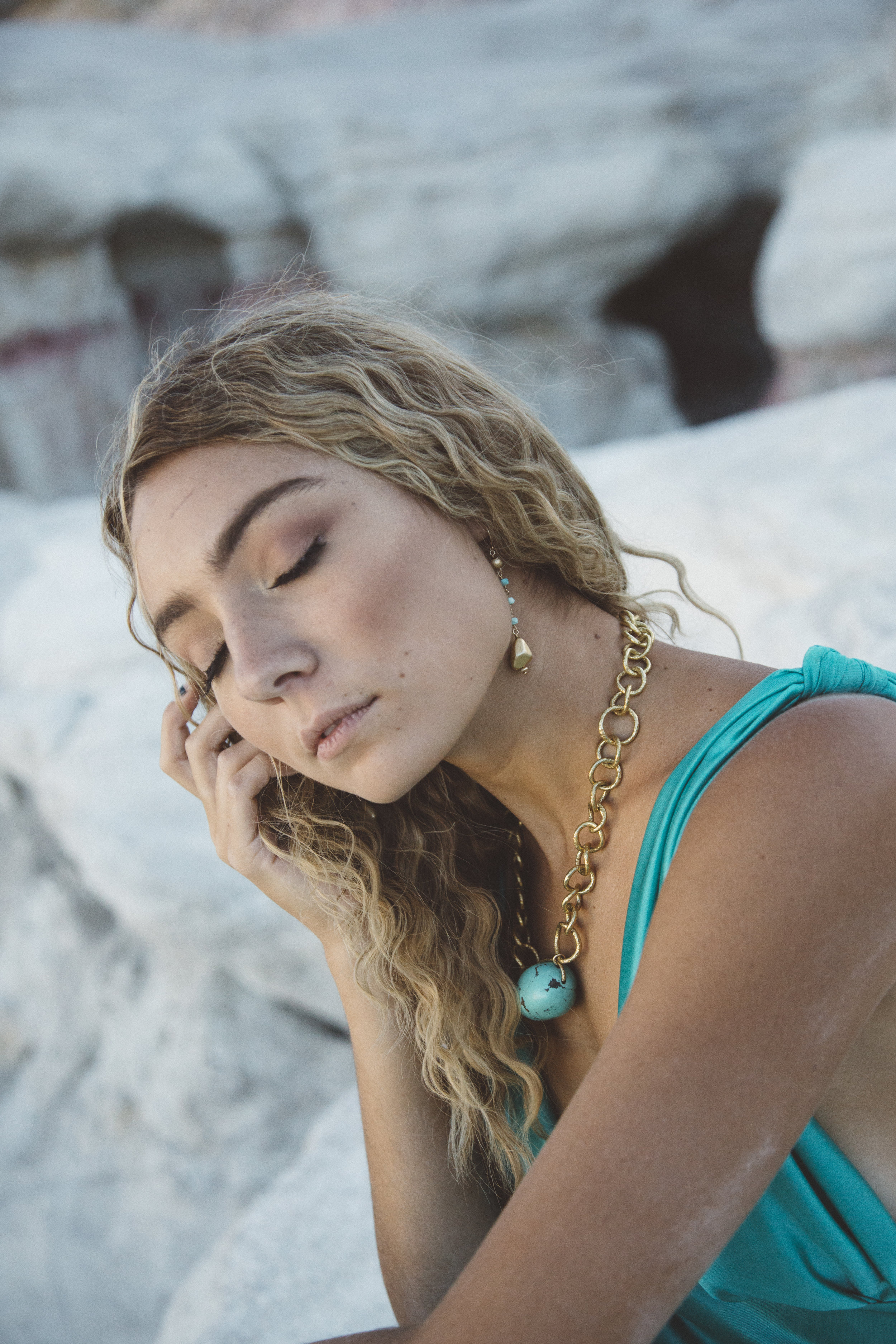 Model wearing a chunky gold chain collar necklace with a turquoise nugget