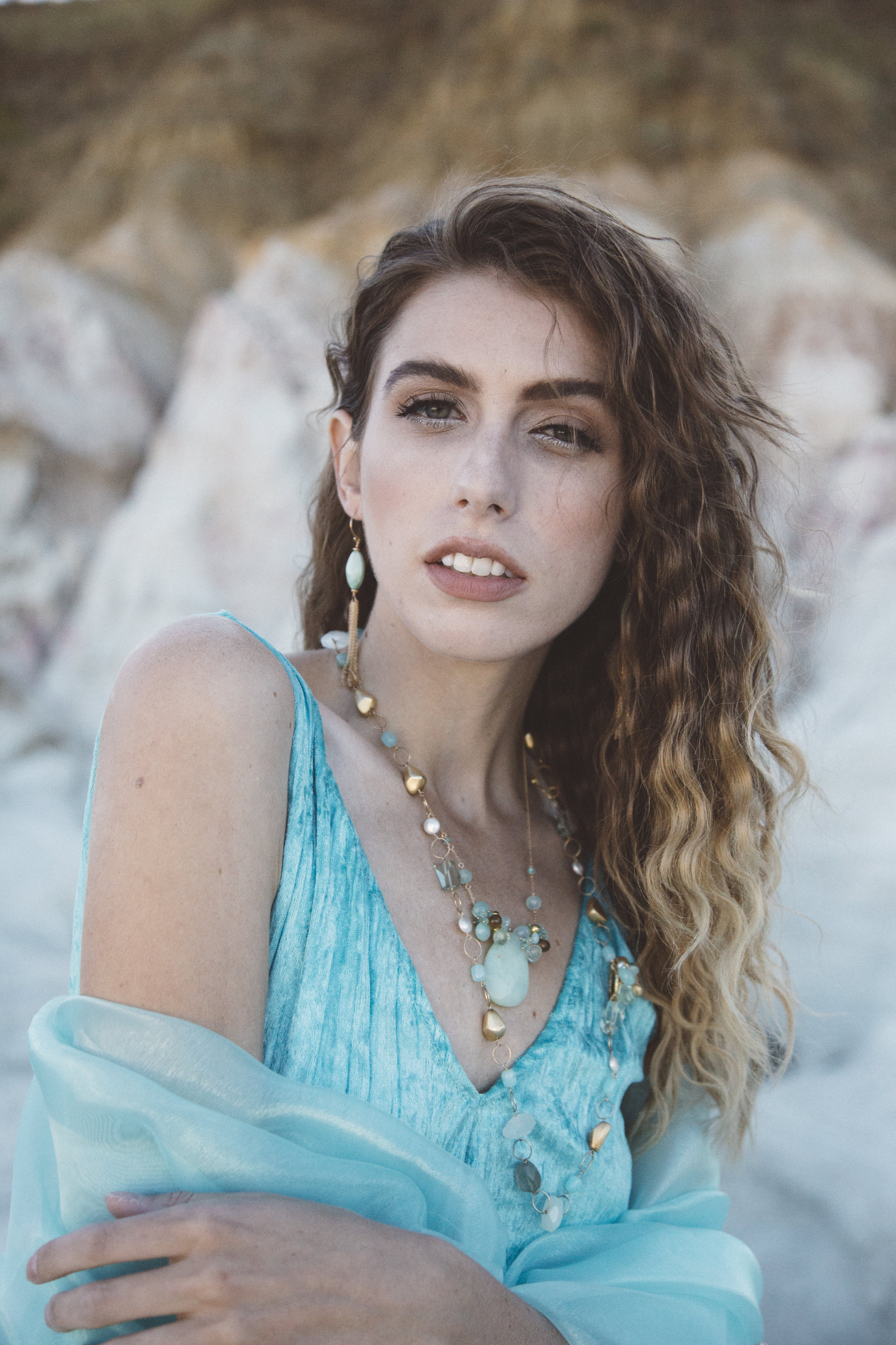 Model wearing a marquis shaped amazonite with gold chain tassel earrings