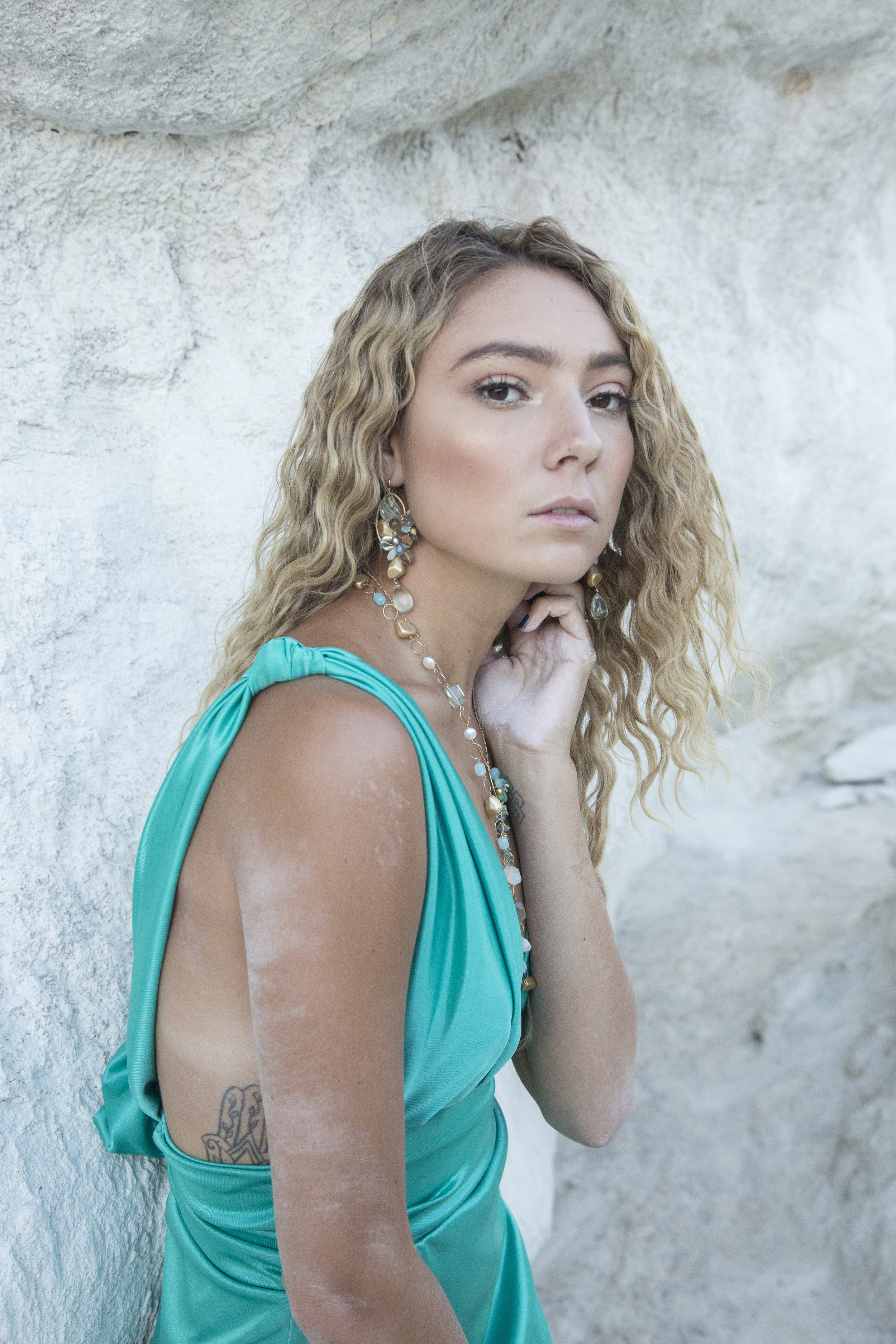 Model wearing gemstone statement earrings