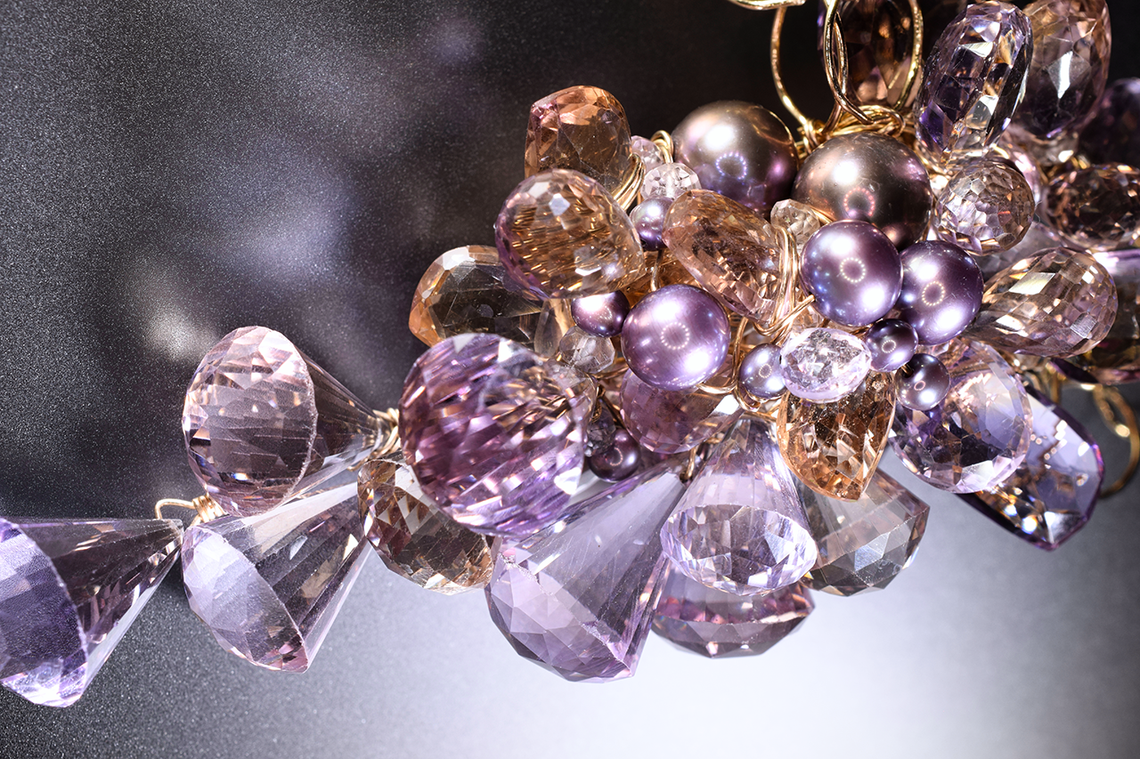Details of a pink amethyst, ametrine, pearl and gold statement necklace