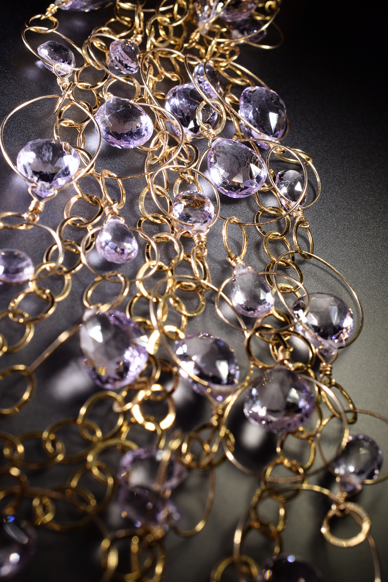 detail of a pink amethyst multi strand gold link statement bib necklace