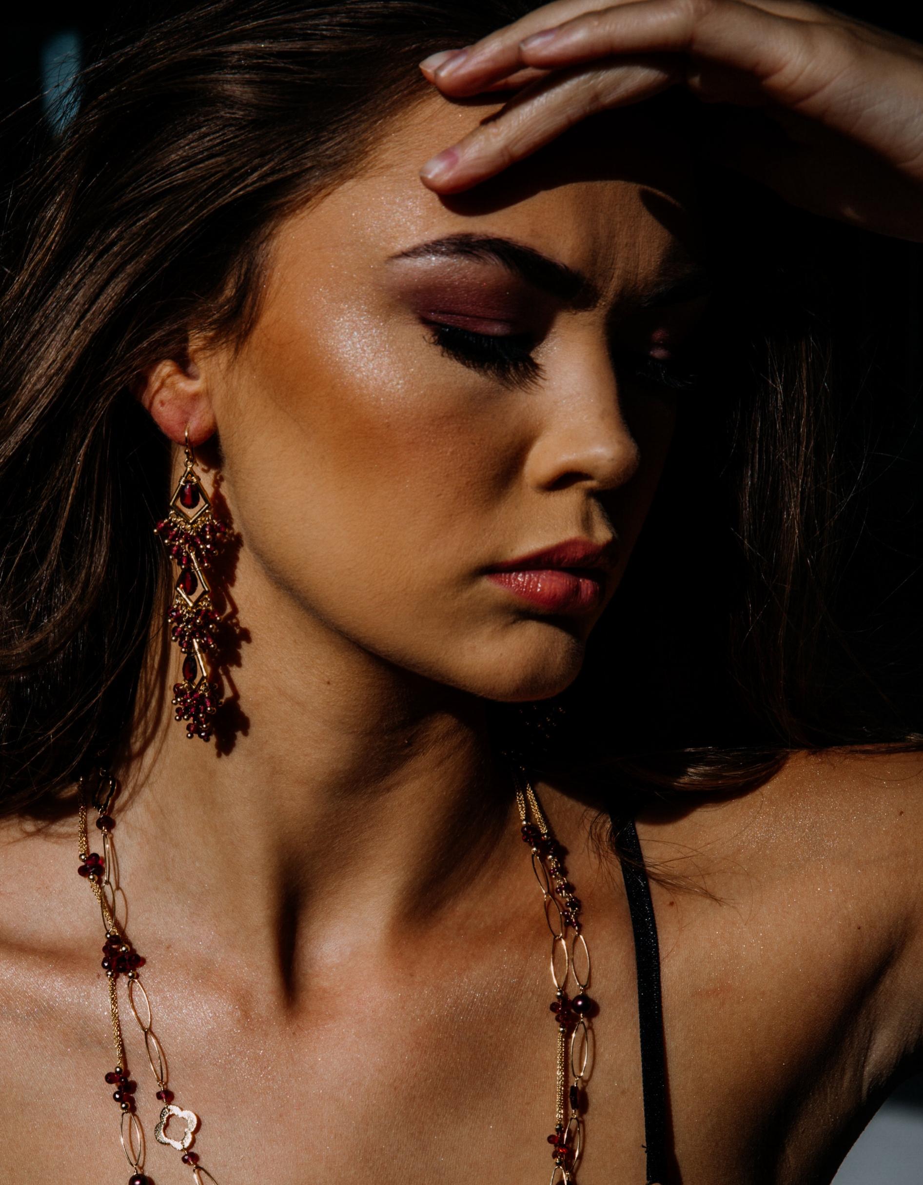 model wearing garnet statement earrings