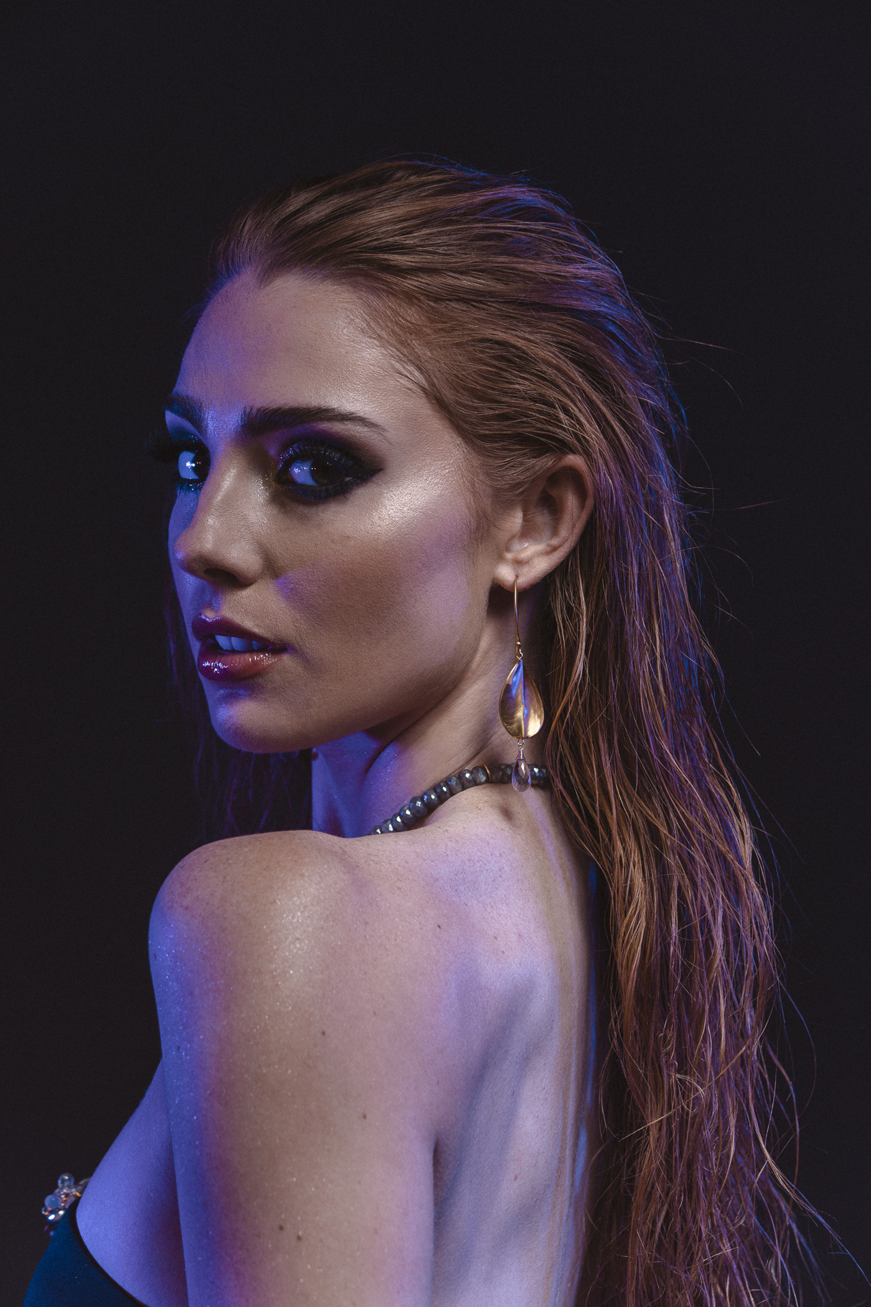 model wearing brushed gold oval drop with gemstone briolettes accents