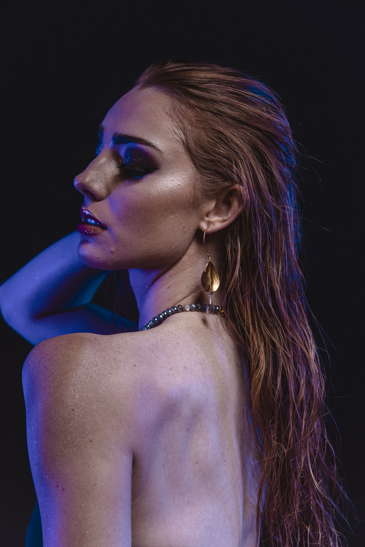 model wearing brushed gold oval drop with gemstone briolettes accent