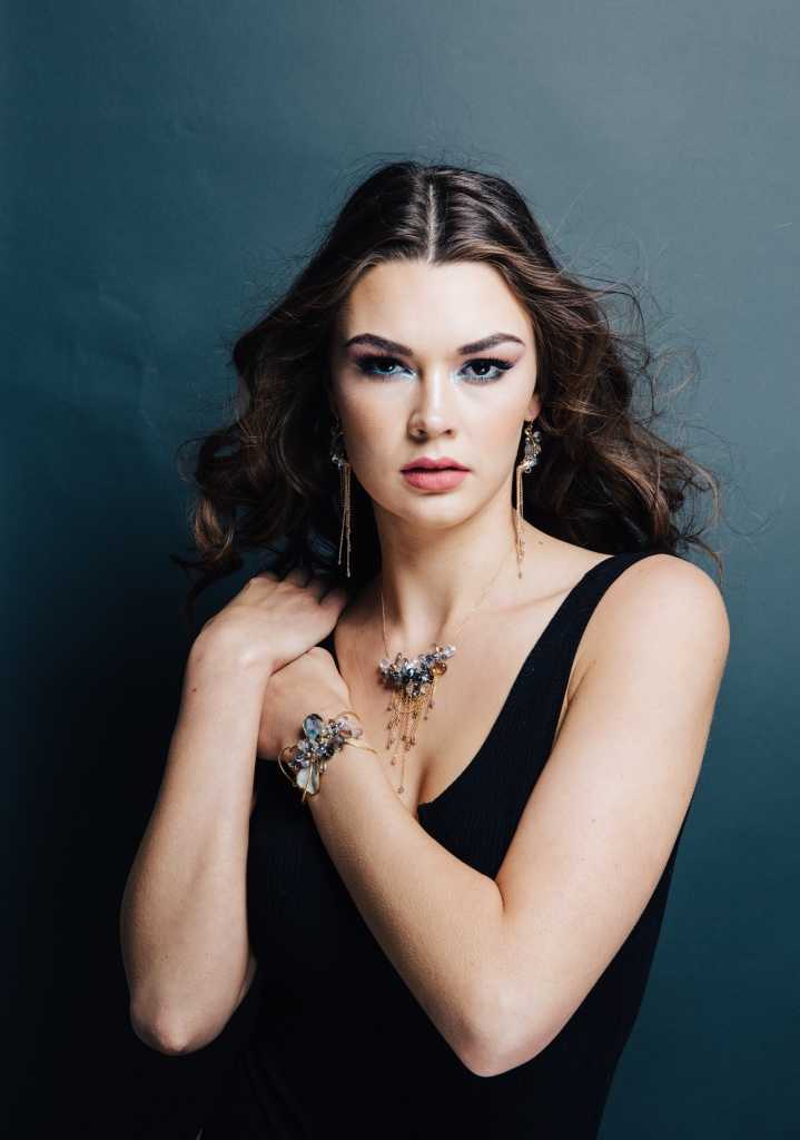 model wearing multi-drop gemstone necklace with delicate gold chains