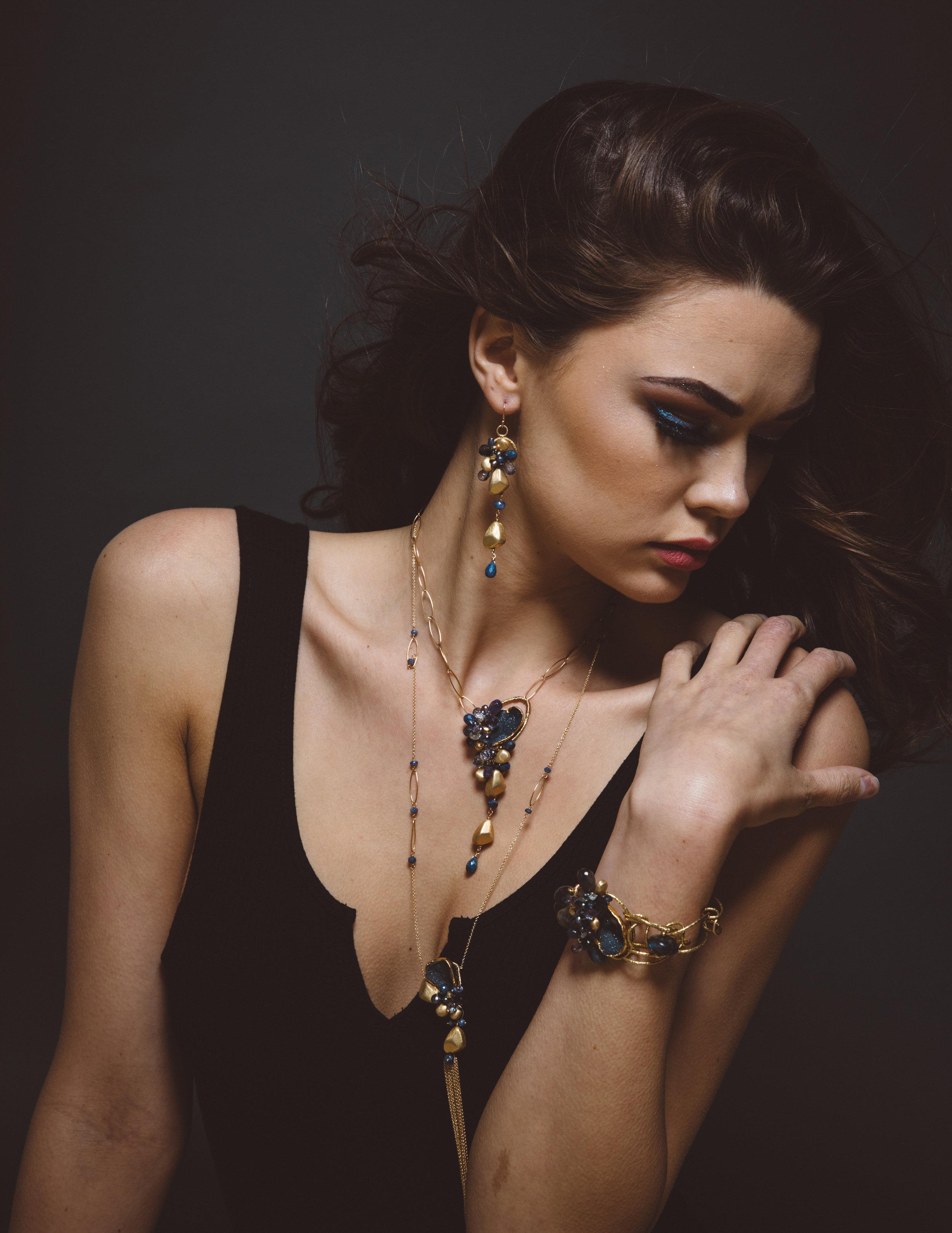 model wearing gemstone and gemstone gold drop pendant necklace