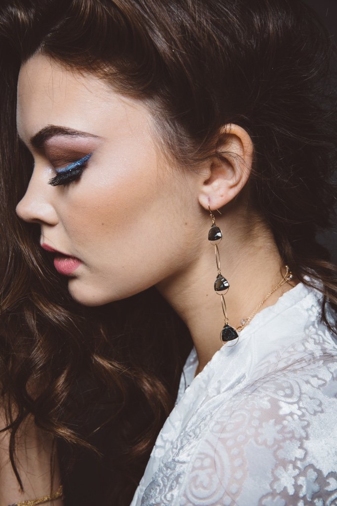 model wearing fancy trillion cut quartz triple drop gold earrings