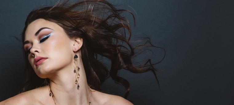 model wearing fancy trillion cut quartz multi chain link drop earrings