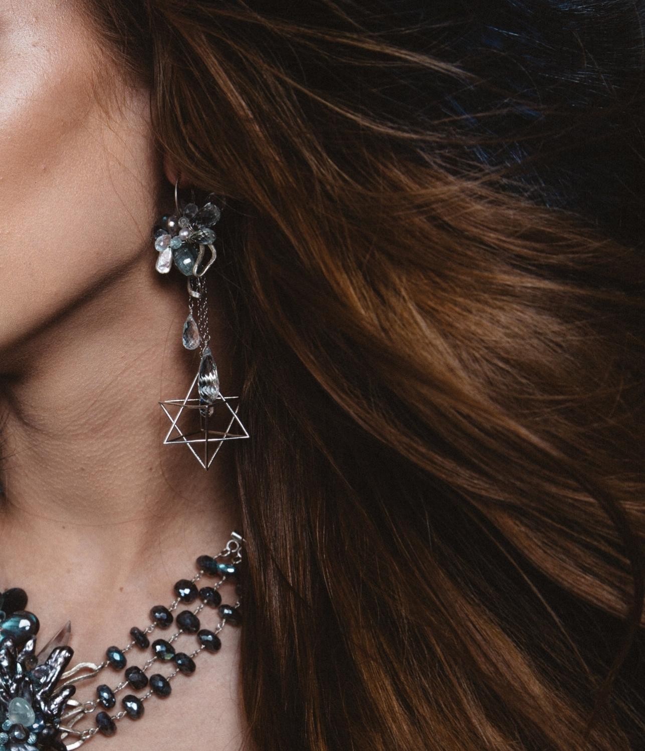 model wearing gemstone statement earring with 3D printed sterling silver merkabas