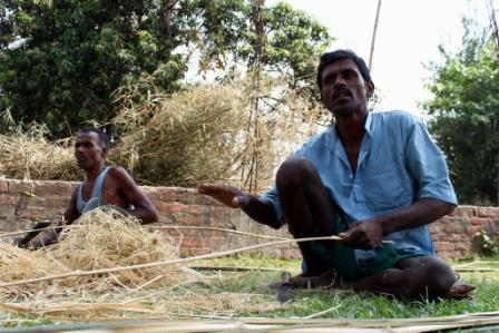 Neighbours at work with bamboo rods, to be used as walls for homes, Araria, 1 May 2016