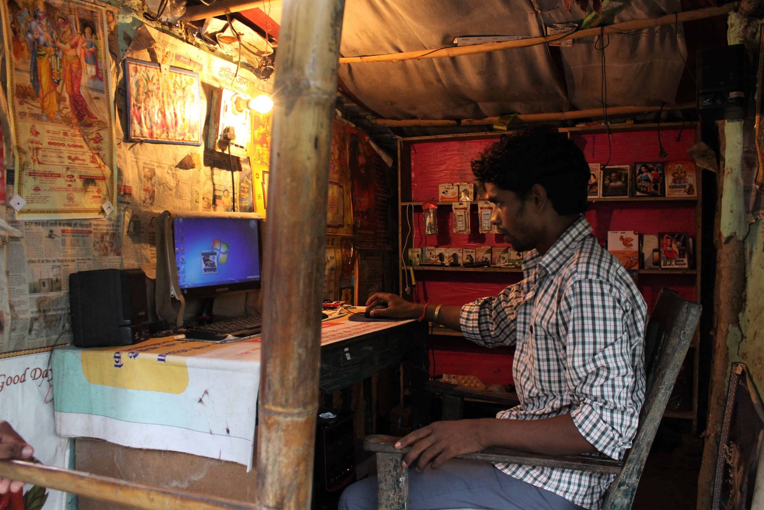 A young man operates a desktop computer at his shop. Credit: Atul Anand