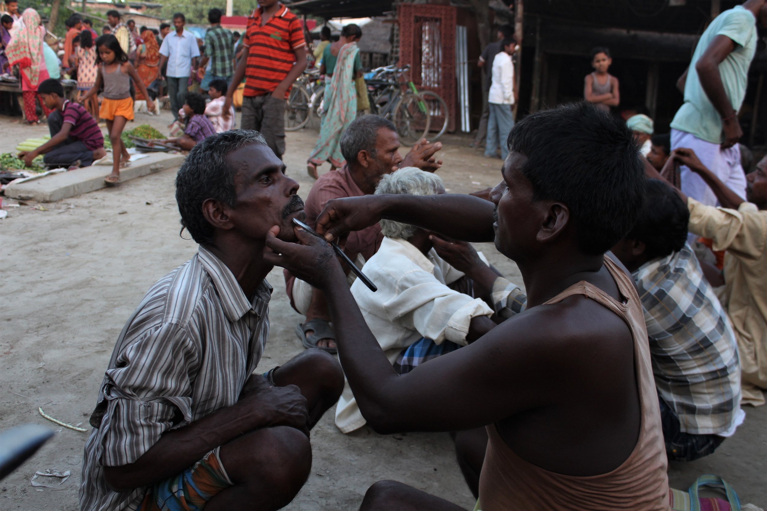 A barber grooms a man in the village market. Credit: Atul Anand