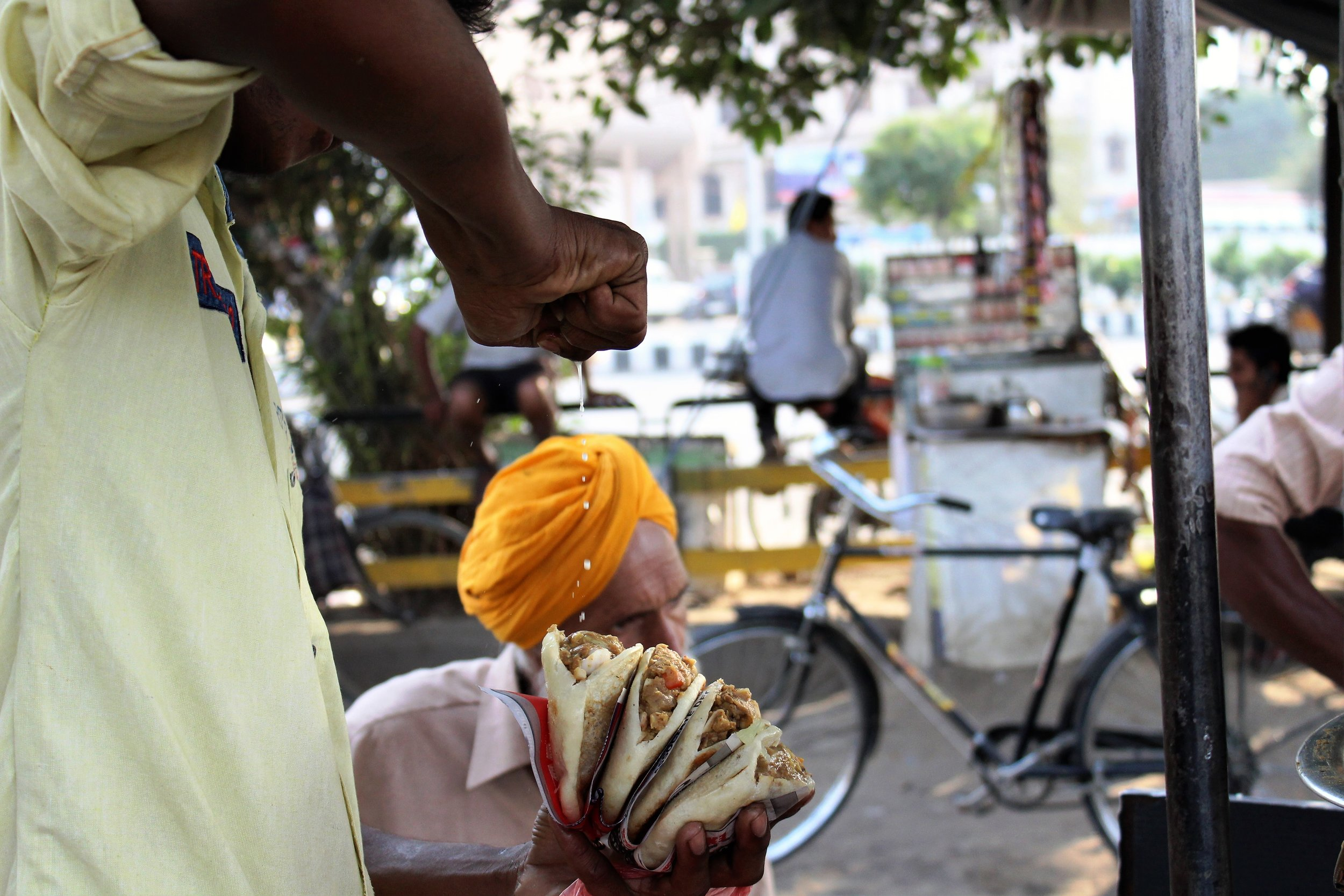 A street vendor squeezes a piece of lemon on Chhole Kulche, a type of street food. Credit: Atul Anand