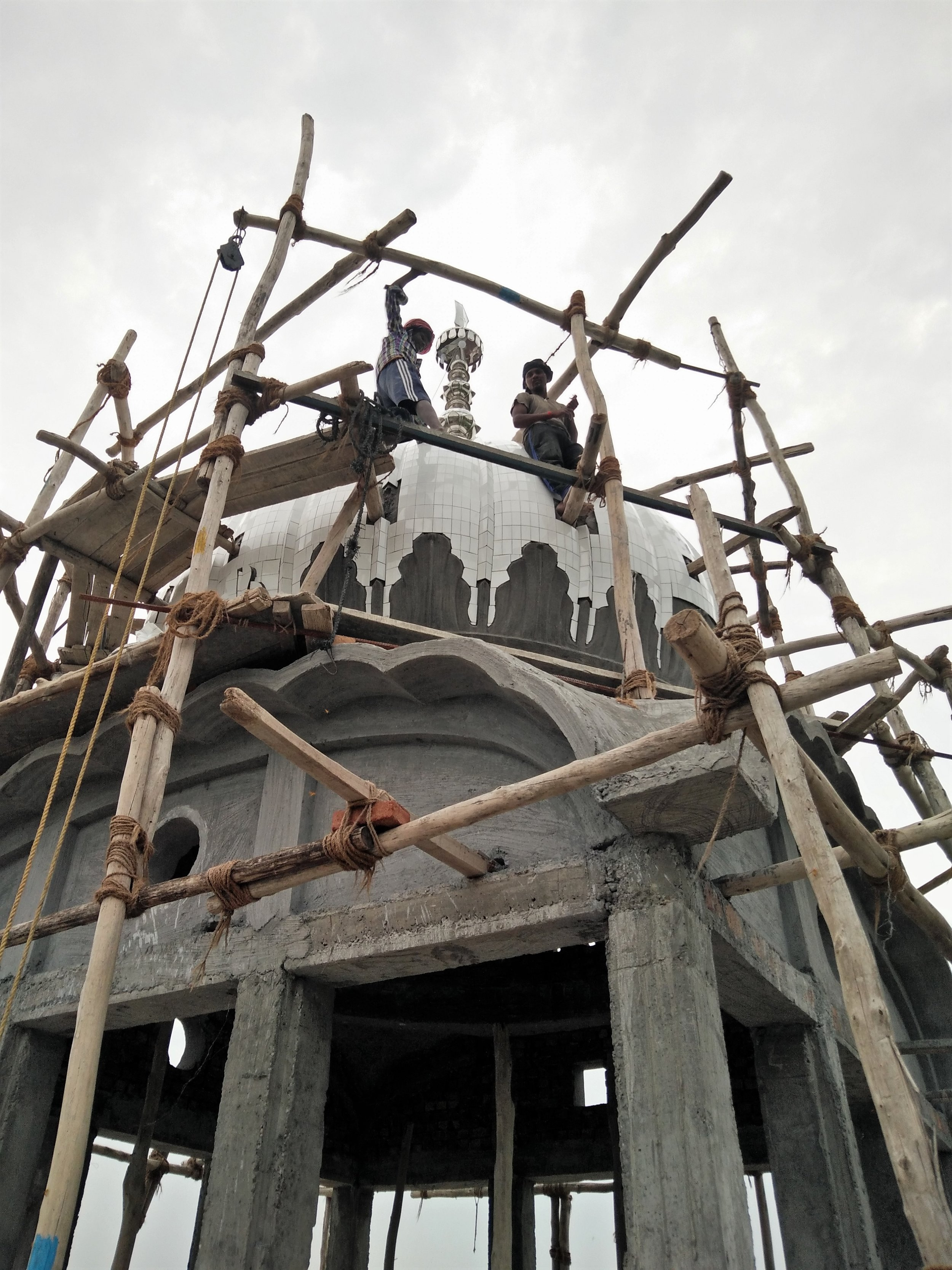 Migrant workers build Gurudwara dome. Credit: Ankur Jayaswal