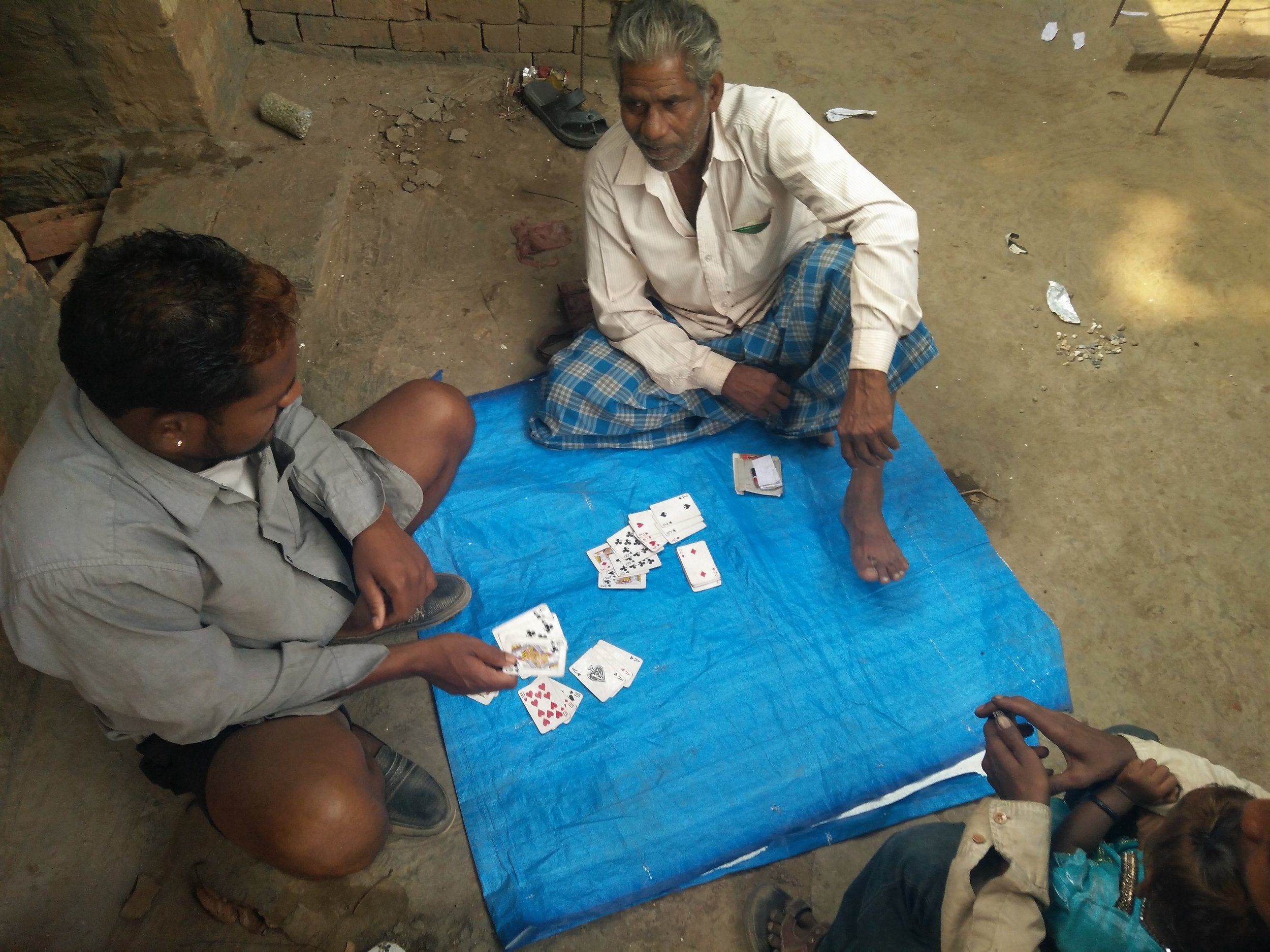 Migrant workers play cards  in their free time. Credit: Ankur Jayaswal