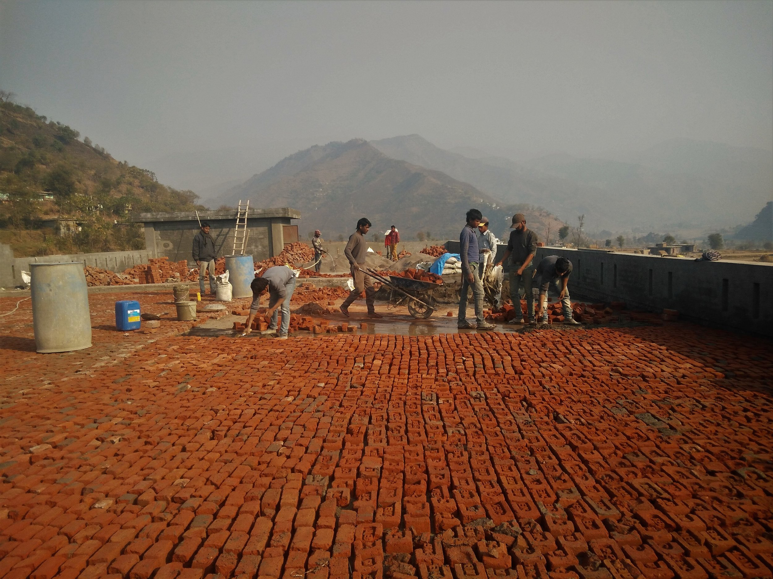 Migrant workers constrcut a water resistant roof for the school building in Poonchh. Credit: Ankur Jayaswal