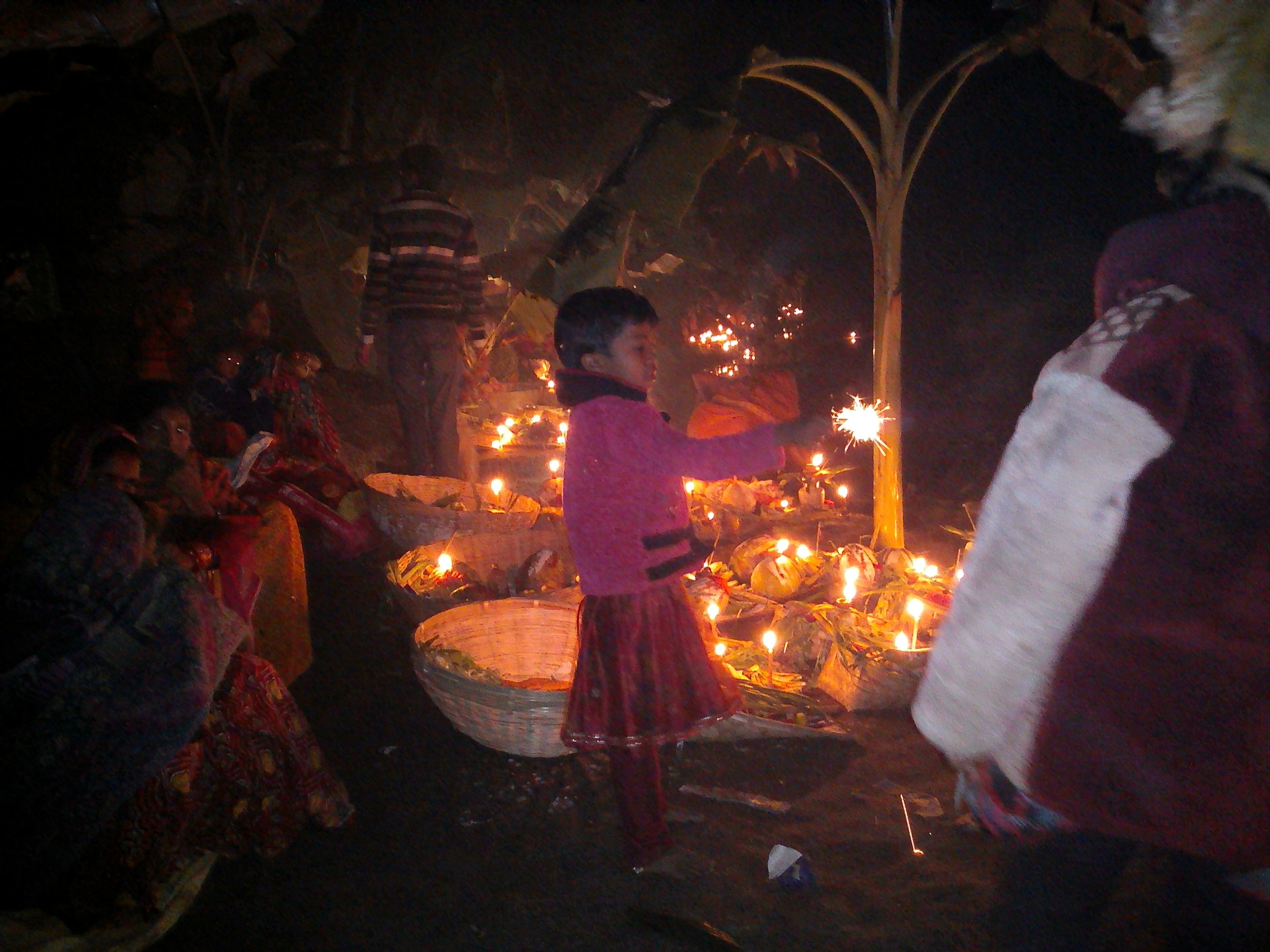 A child lights a sparkler in the morning while observing Chhath prayer. Credit: Zaheeb Ajmal