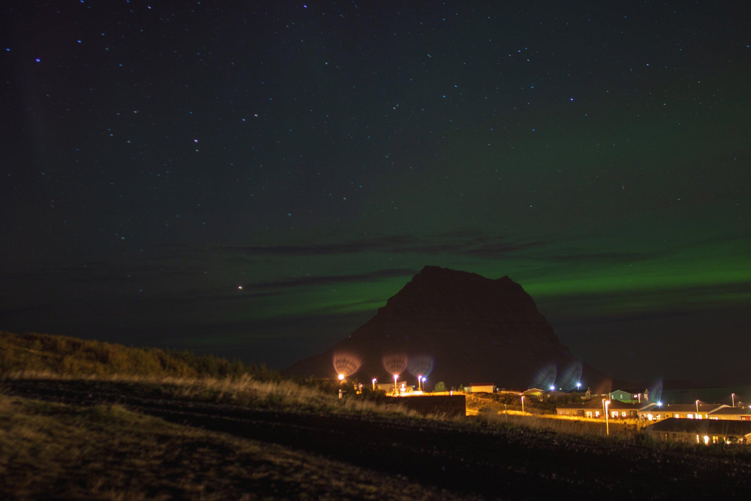 Aurora: Got 'em! Kirkjufell with the town of Grundarfjörður in the foreground and the Aurora Borealis behind.