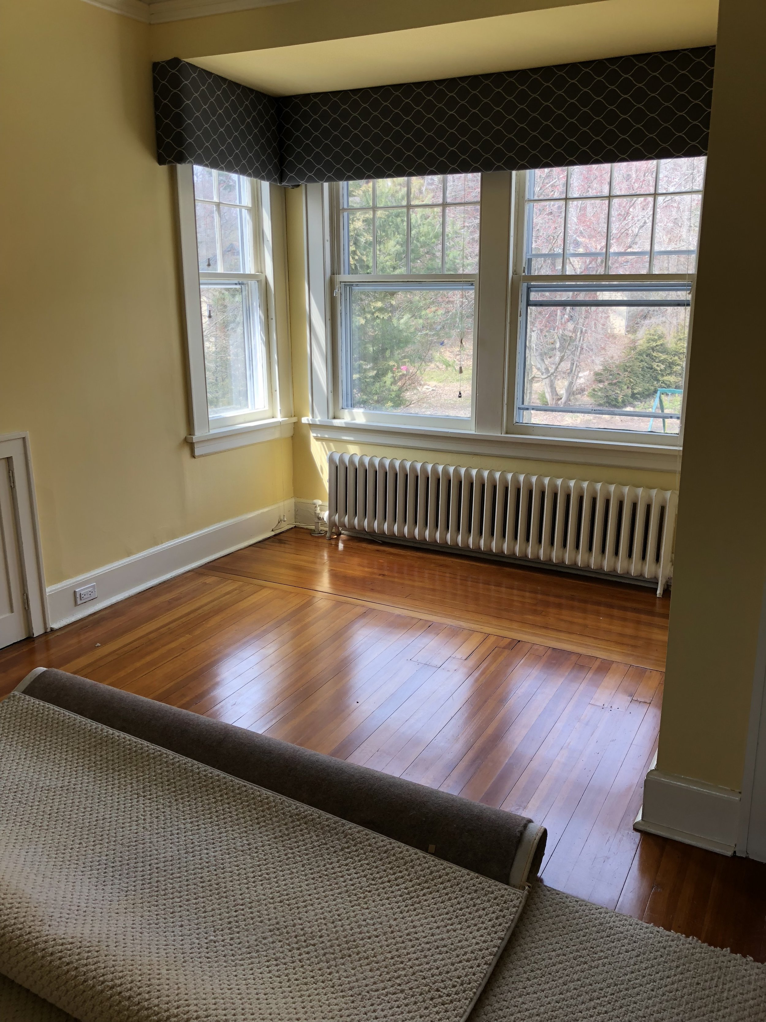 "The ""before"".  The different orientation of the hardwood floor in this part of the room drives me insane! It must have been patched (poorly) at some point, and it creates a major eye sore."