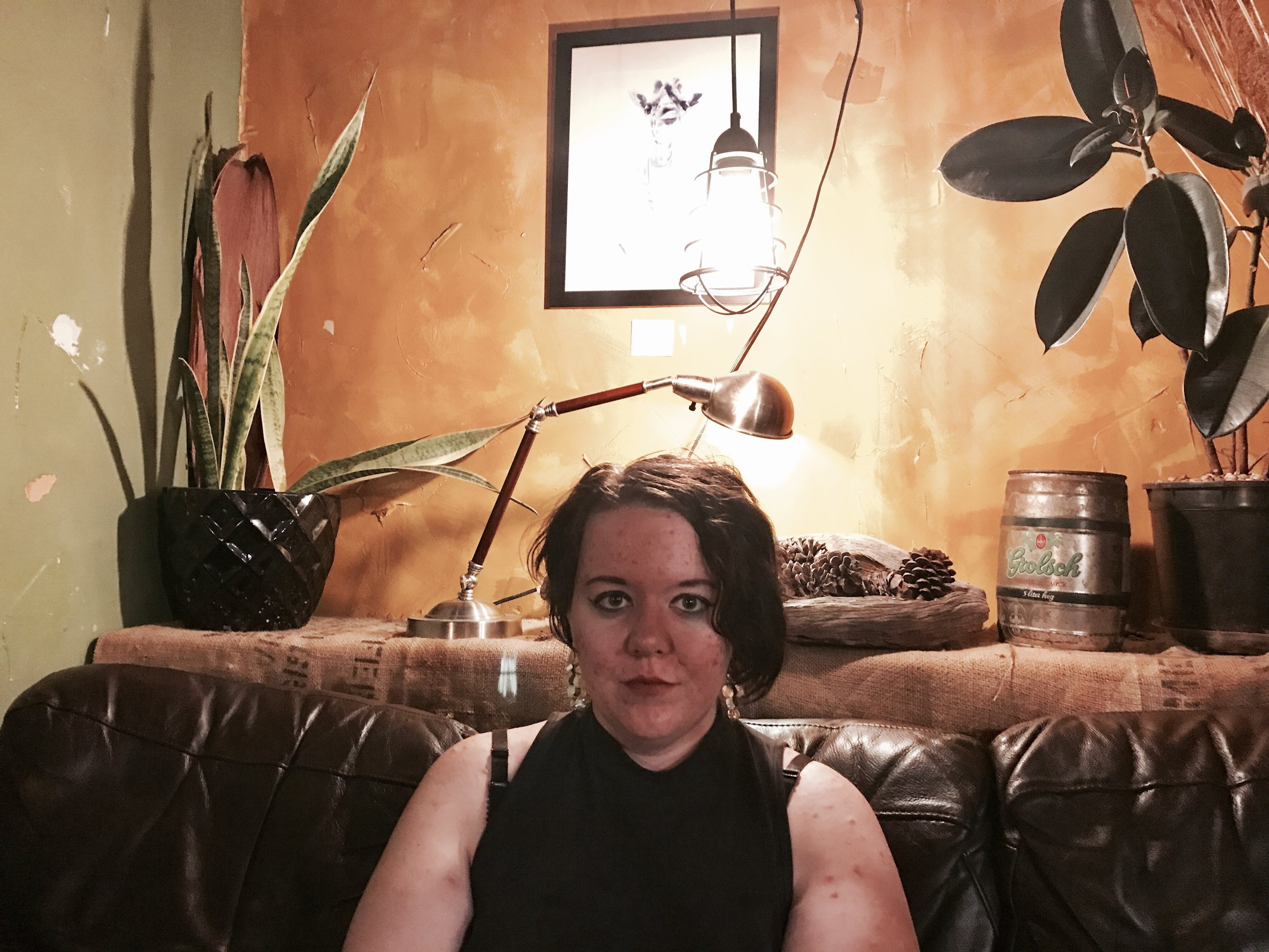 "A photo of a person from the chest-up, looking directly into the camera, sitting on a leather couch. The background behind her is a dark orange and an olive green. On the wall behind her there's a picture of a giraffe. There are many inanimate objects on the mantle behind her and the couch: two plants, two lamps, a bowl full of pinecones, and a small barrel that says ""Golsch""."