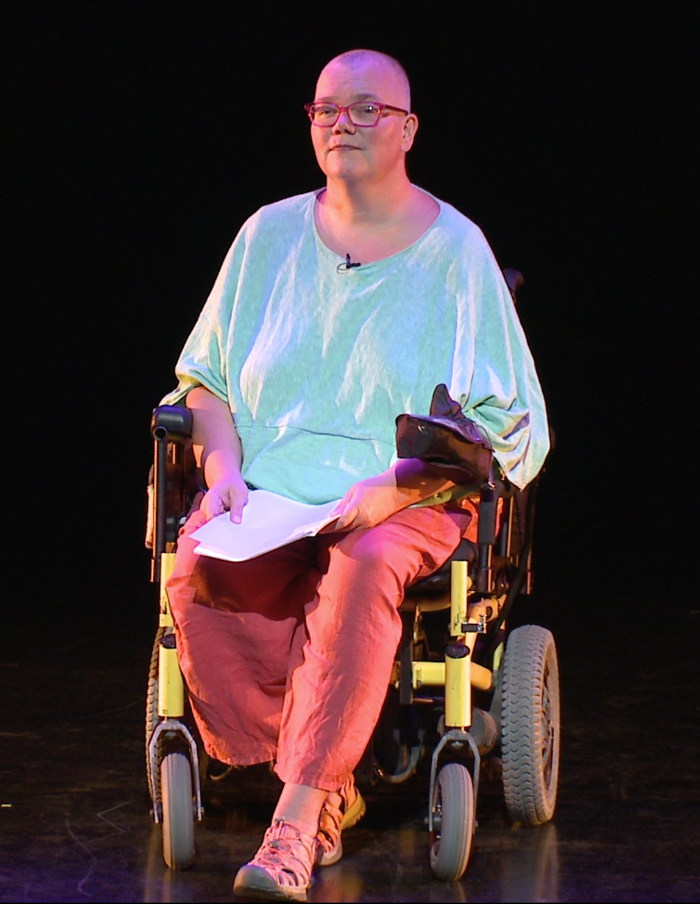 A large white woman in a wheelchair in a dark theatre, short-shorn grey hair, glasses, primary color clothes, with a poetry manuscript in her hand, looking at the camera.