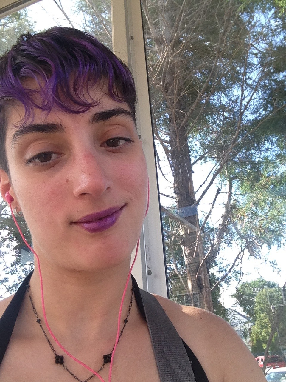 A Caucasian femme with shaved brown hair, purple bangs and lipstick, and brown eyes smiling with her head tilted against a backdrop of trees.