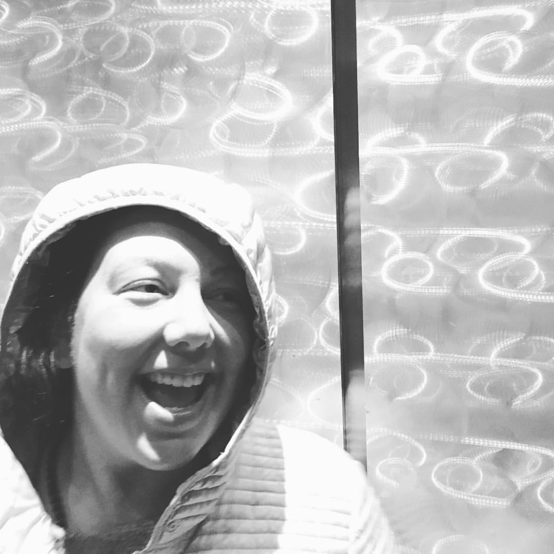 Black and white photo of a woman laughing, wearing a winter coat. Her face is partially shadowed by the coat's hood, and she is looking off to the right edge of the frame. She occupies the bottom left-hand corner of the picture. She is standing inside an elevator, and the elevator's reflective walls match her silver winter coat.  Photo by Kathleen Maris Paltrineri.