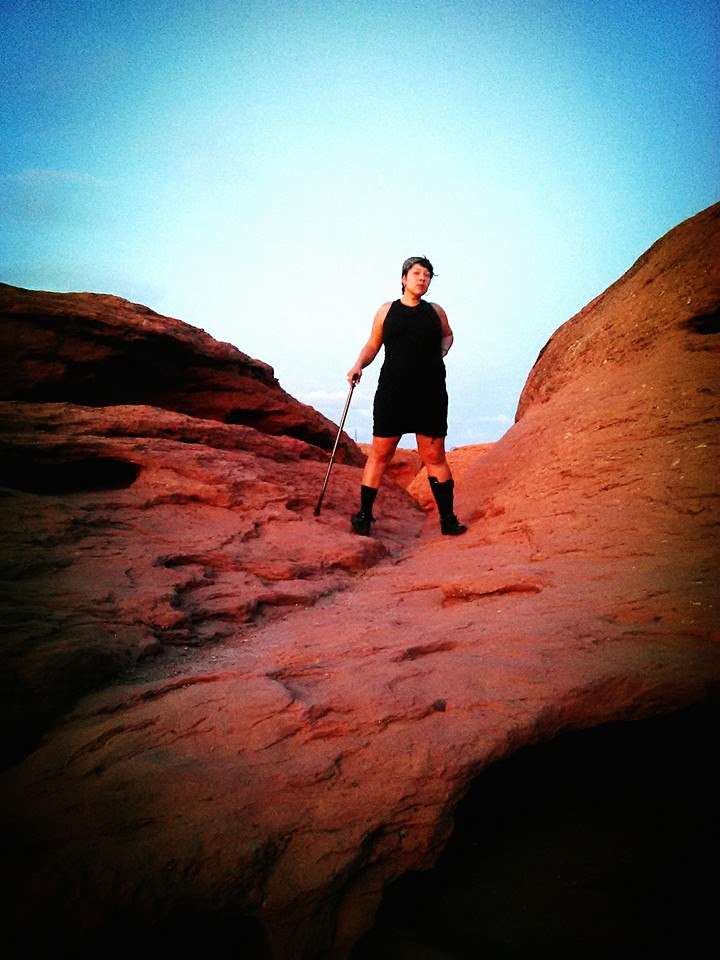 A tan woman with short dark hair in a black tank dress is standing on a huge deep red desert rock formation looking into the camera. She is silloutted against a bright blue sky with one hand on her hip and the other hand on her walking cane.