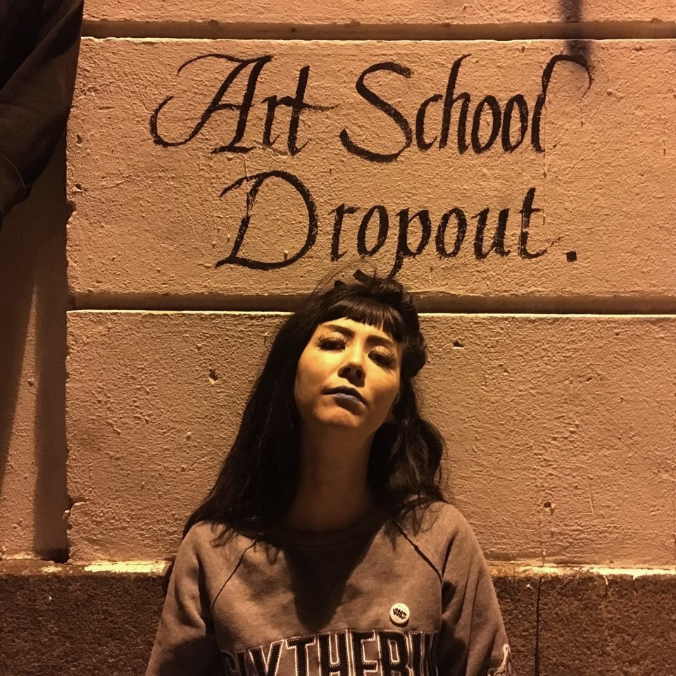 """A portrait, taken in low light, at night. Centered, in the lower half, is a person in stark shadow, with her head tilted back against a wall. She wears blue lipstick, false eyelashes, and has exaggerated eyebrow makeup. Her black hair is cut in blunt bangs and falls over her shoulders. She wears a gray sweatshirt that says SLYTHERIN in the style of athletic team logos. Above her heart is a small pin with black teeth. Above her head, on the wall, is a calligraphic tag that says, """"Art School Dropout."""""""