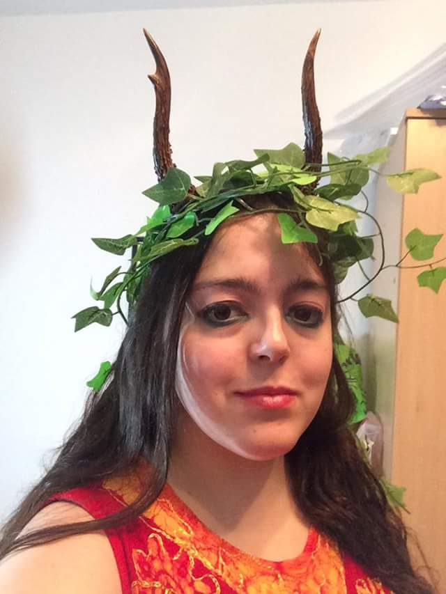 A portrait shot of a person with long dark hair, light skin, and heavy green eyeliner, who is smiling slightly. They are wearing antlers and a crown of ivy, and a red and gold patterned top.