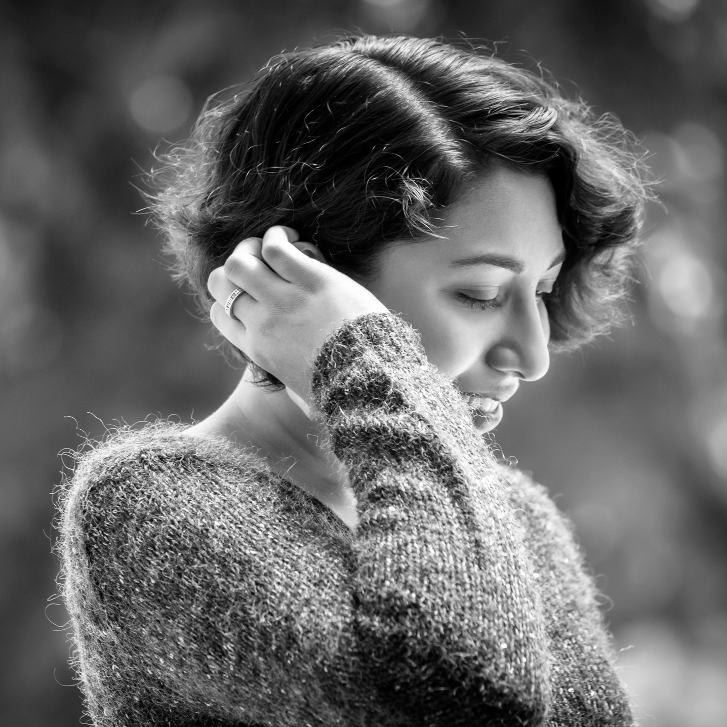 A black-&-white side shot of a young brown woman in a dark grey sweater. There's a ring on her middle finger & her hand is raised, curling her short hair behind her ear. She is smiling slightly & looking downwards.