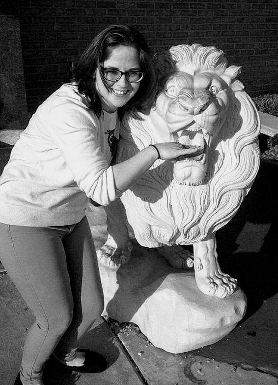 Black and white photo of a young woman with medium-length dark hair and glasses. She is in a stooped position alongside a large statue of a roaring lion. Her right hand is in the lion's mouth.