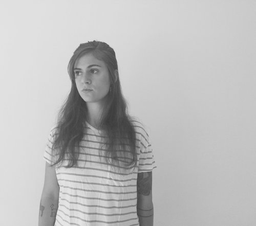 A black and white photo of the author against a pale background. She is wearing a white t-shirt with dark horizontal stripes. She has long dark hair, and is looking off to the side.