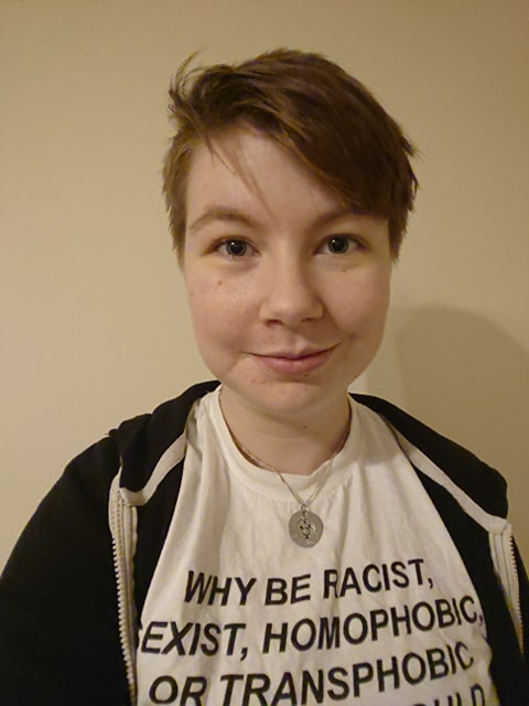 The author is stood in front of a plain wall. They are smiling into the camera. They have brown hair, cut short, and are wearing a white t-shirt with black text and a black hoodie.