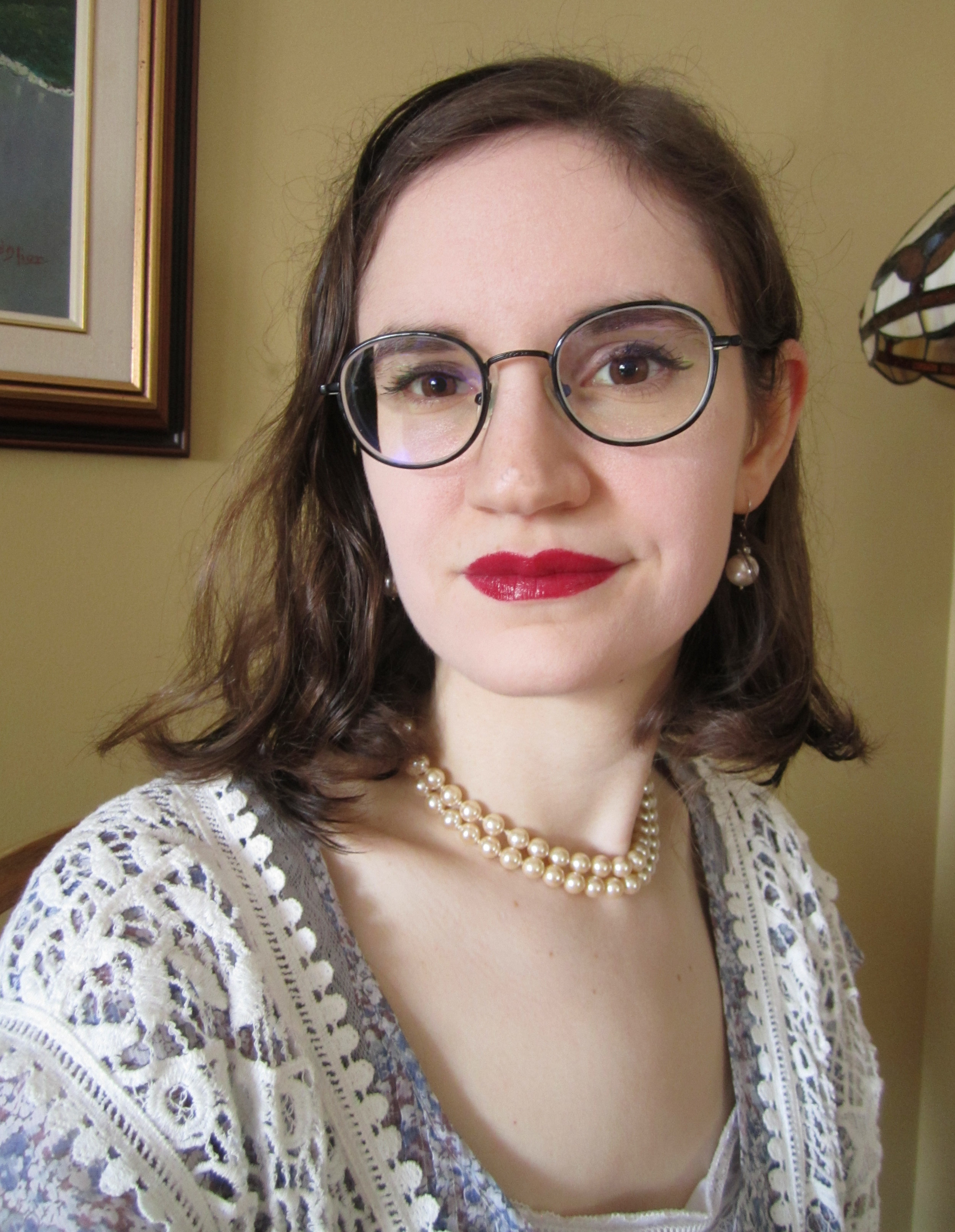 Picture shows the head and shoulders of a white woman with medium-length brown hair, seated against a cream-coloured wall. She is wearing round glasses, dark red lipstick, pearls, and a lacy shawl draped over a pale purple blouse. The edges of a framed painting and a lamp can be seen in the background.