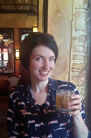A white woman in her thirties sits at a table in a restaurant. She is smiling at the camera and is raising a cocktail in her left hand. She has short brown hair and is wearing a blue shirt with leopards on it.