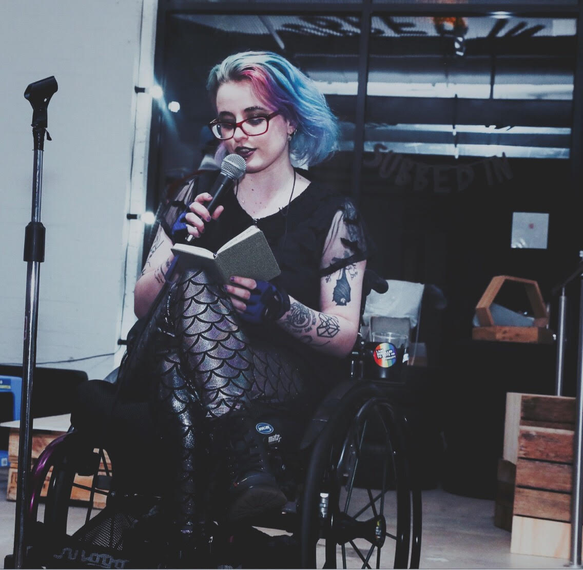 Image shows a white genderqueer wheelchair user with rainbow hair reading into a microphone.