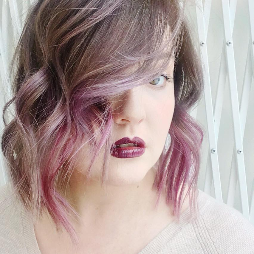The author is stood against a pale background, with crisscrossing metal bars. They have shoulder-length purple ombre hair, and half their face is obscured by a sweeping fringe. One eye is visible from behind it. They are wearing dark purple lipstick.