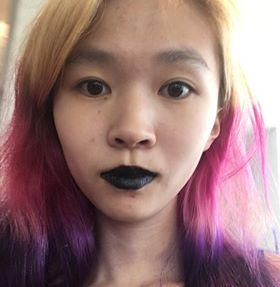 Photo of Caroline Mao. Front facing view, looking directly into camera. Background is a window. Author is only shown from the neck upwards, with black lipstick and blonde, pink, and purple hair.