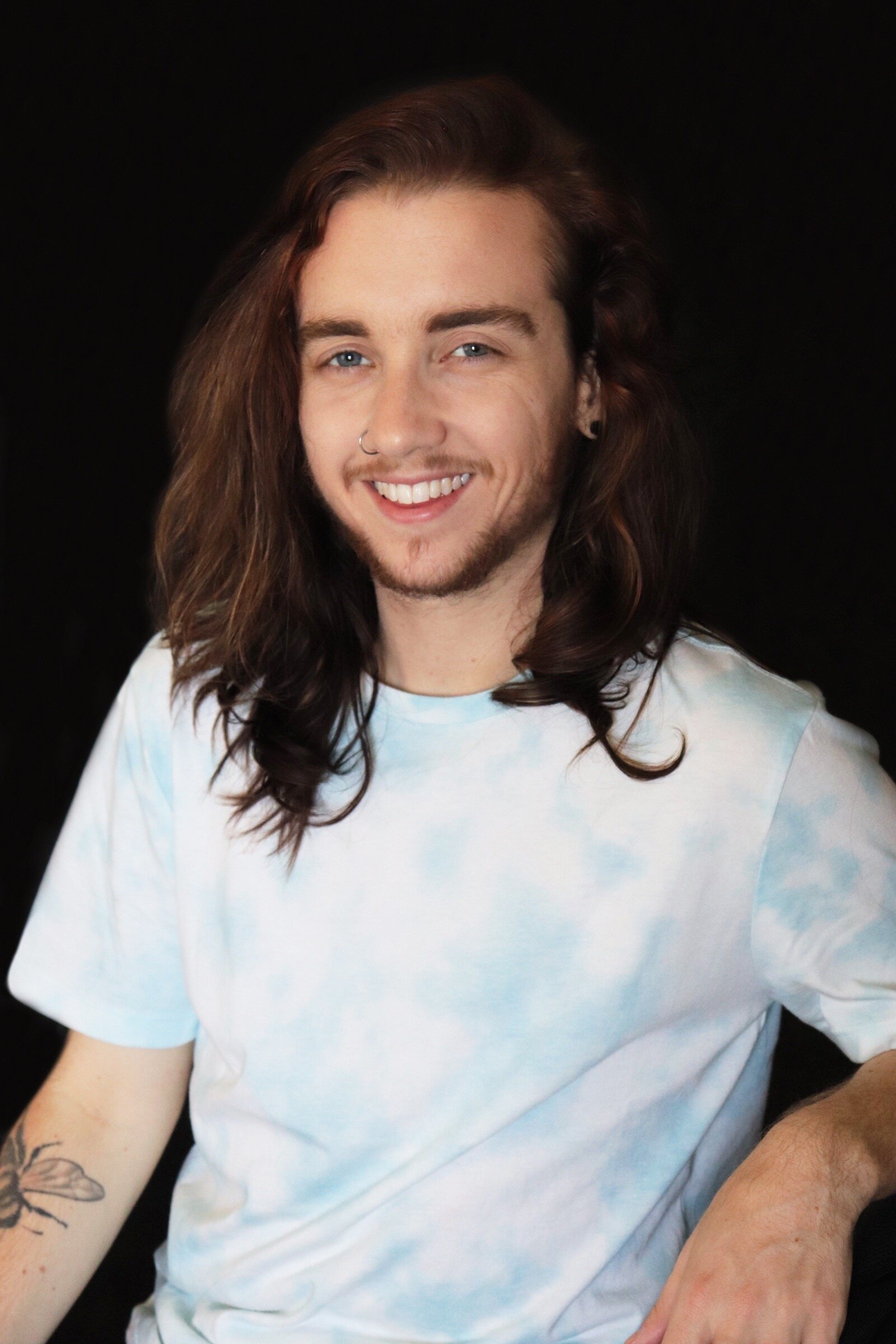 A white non-binary individual with long brown hair smiles for a close headshot. He is wearing a light blue tye-dye shirt against a black background.