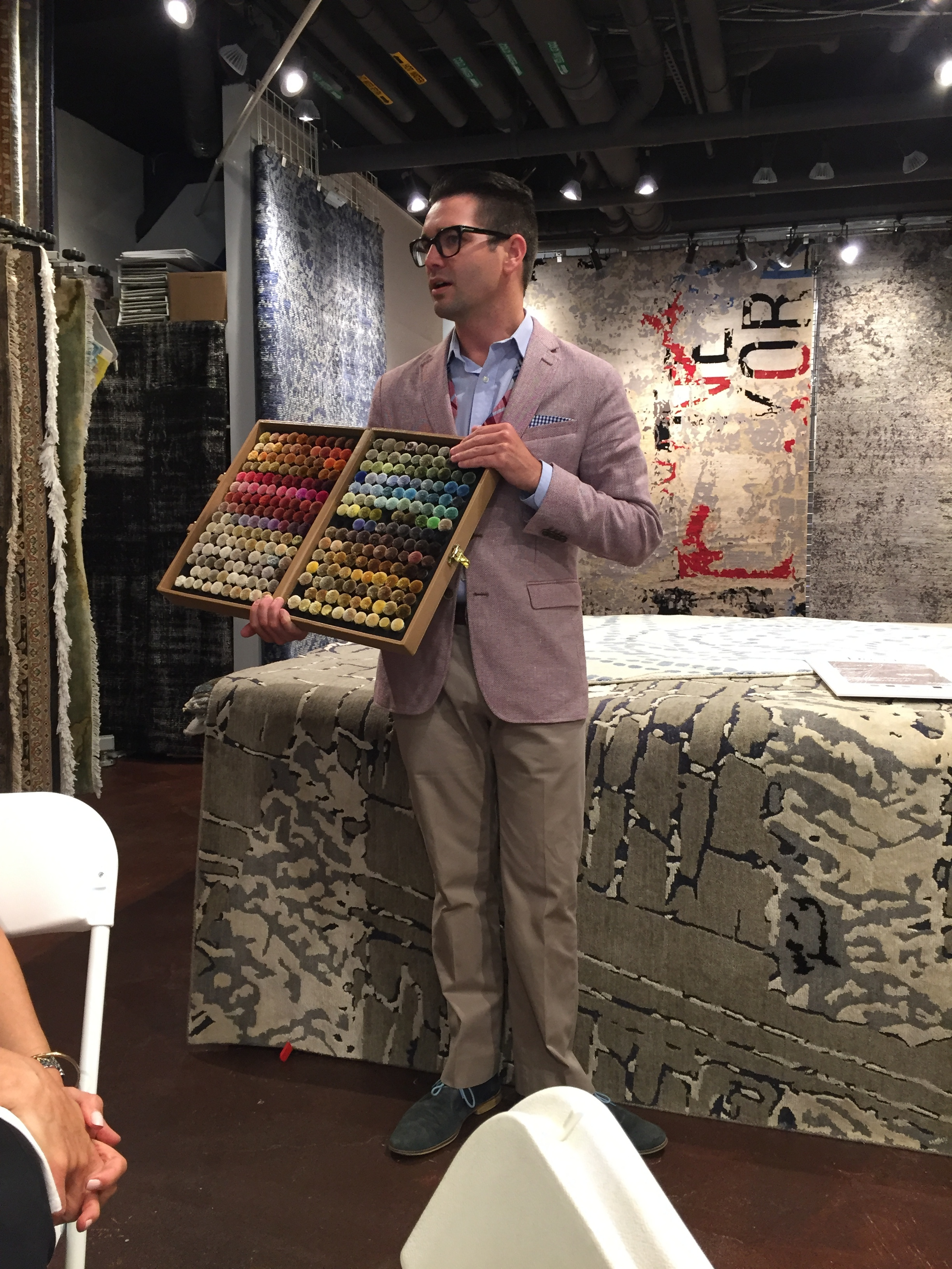 Eric showing color poms, which are available for those who would like to order rugs to match their design needs.