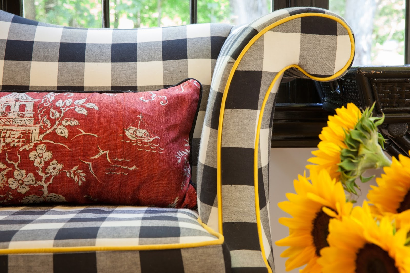 """Inspired by a photo of Grace Kelly in a red dress, lounging on a black and white sofa with yellow pillows, Kim wanted to create a space that was classic, fun, and fresh.  The linen toile from GP & Baker keeps the black and white buffalo check from looking too country. To tie the colors together, she added a yellow trim to the seating, and the ceiling was painted San Pedro Morning, by Benjamin Moore. """"Even on a snowy winter day, my house feels like the sun is shining!"""" says Kim."""