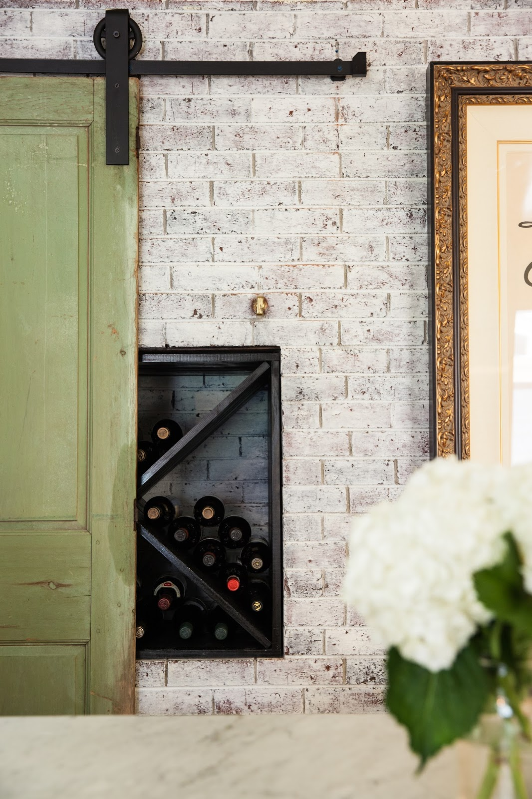 Kim found a piece of wall paneling from Old House Parts in Kennebunk, ME that was a perfect size to use as a door. She hung it barn style, and the original green patina created the perfect balance to the red, yellow, and black color scheme.