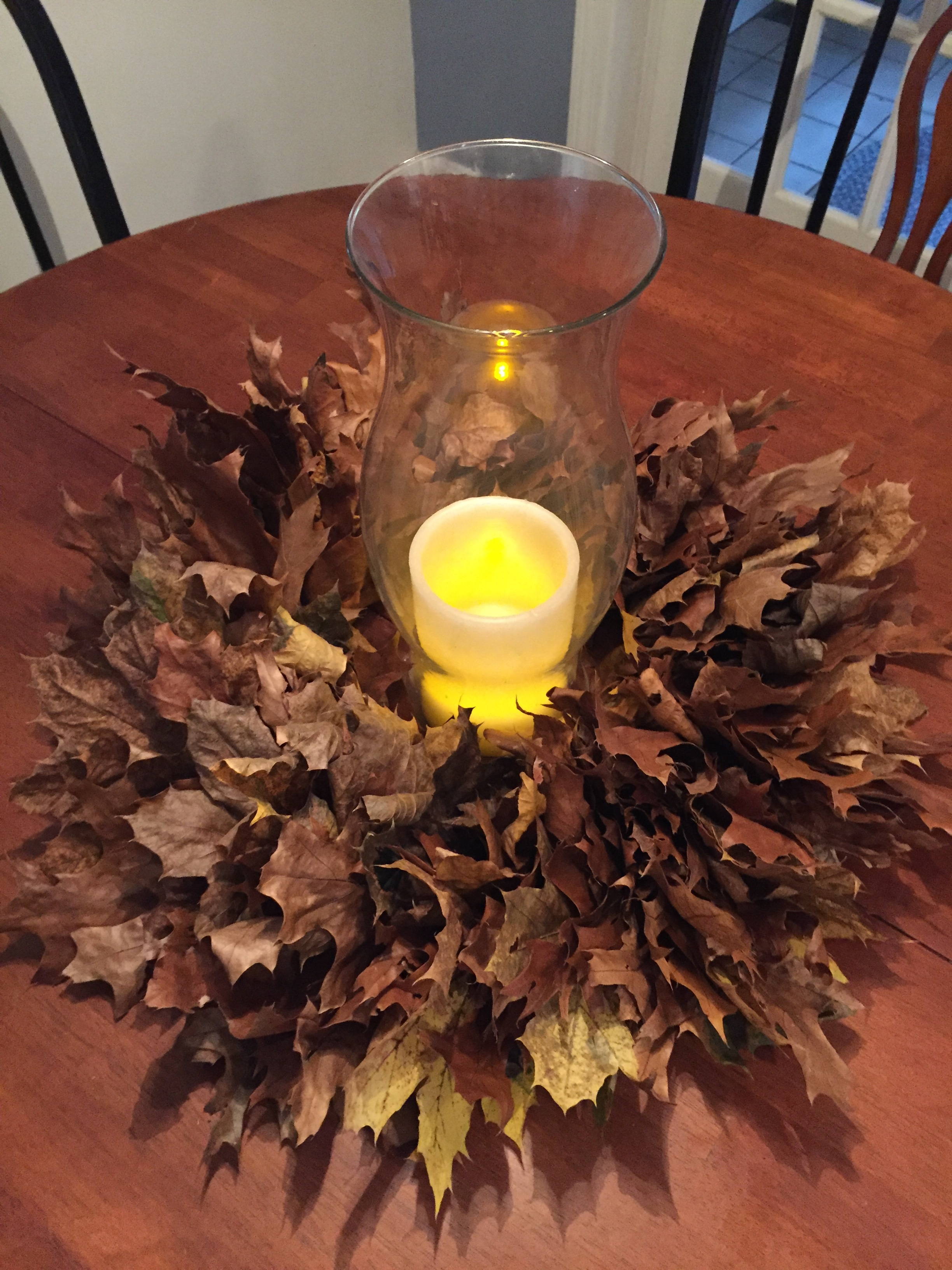 A battery operated candle was used, even with a glass hurricane around the wreath. The dried leaves are highly flammable.