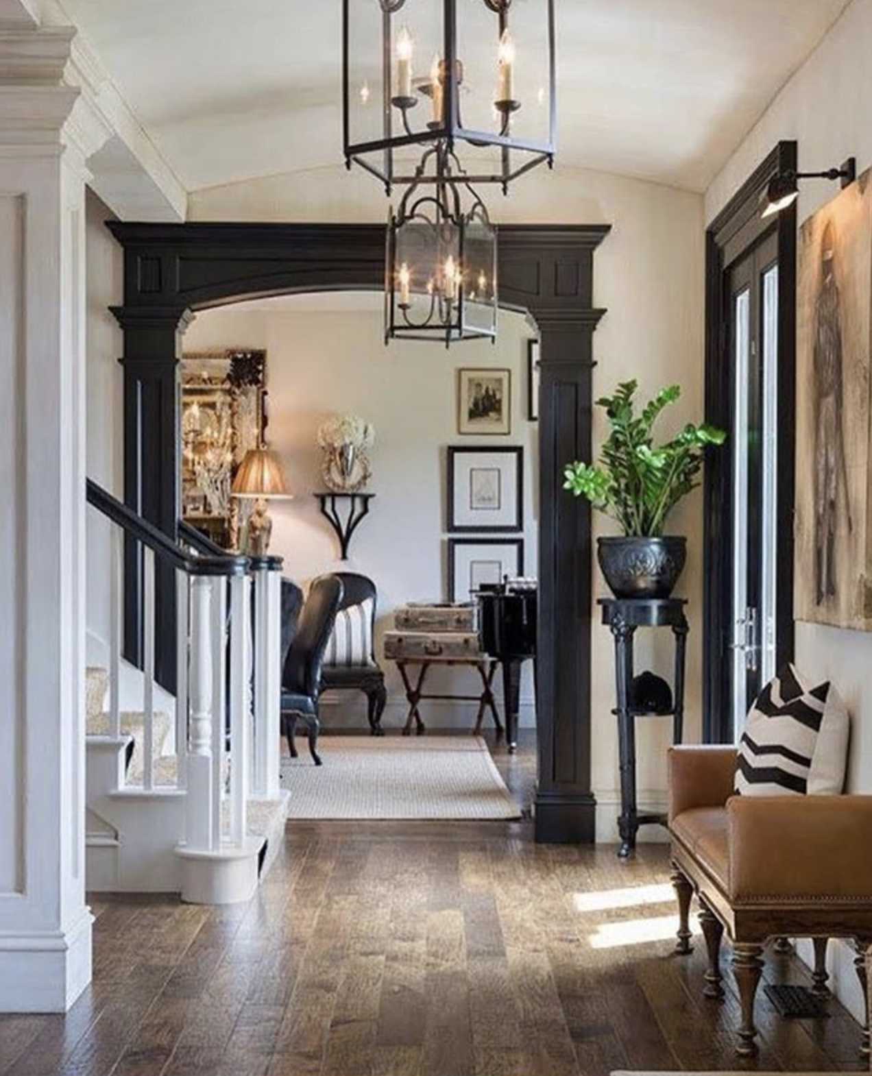 The lighting in this foyer and black doorway molding set the stage for the rest of the home. Designer and source unknown, please contact us if this is your design work or photo for proper credit.